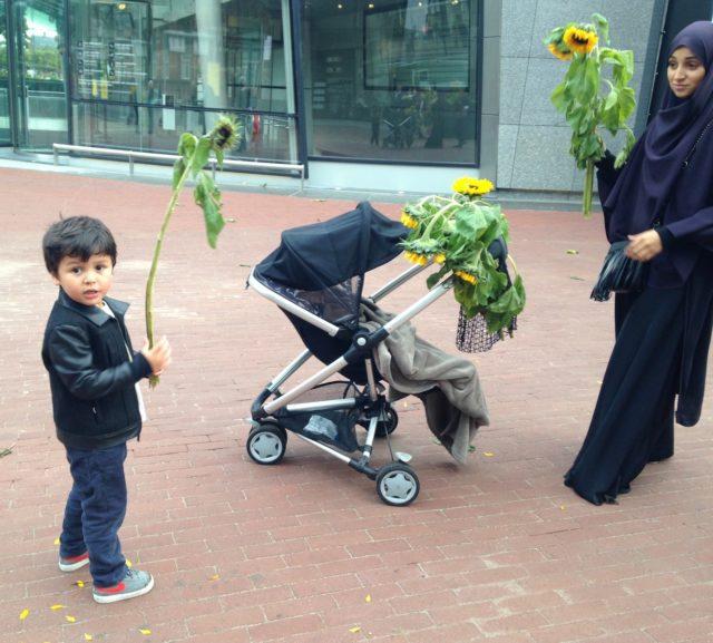 「ひまわりラビリンス」で使われた花を持つ子ども