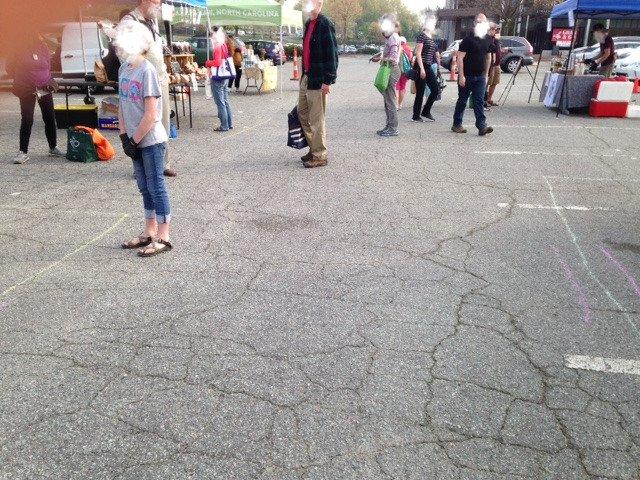 地元のファーマーズマーケットで客が距離を取って並んでいる様子