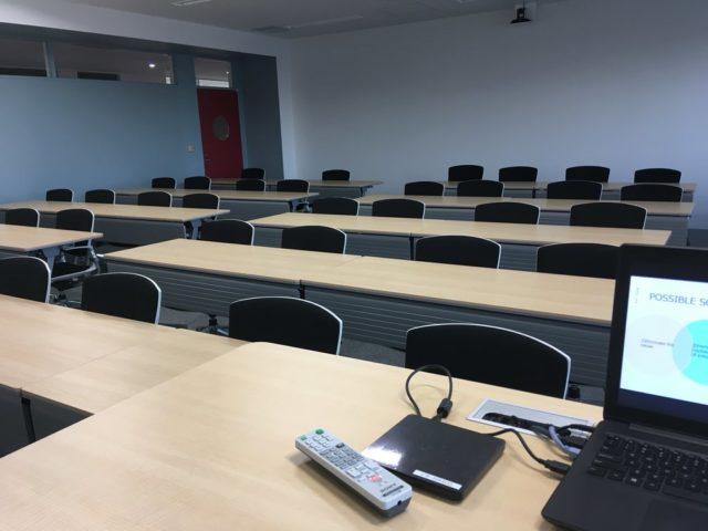 誰もいない教室でパソコンに向かって話す Zoom 授業